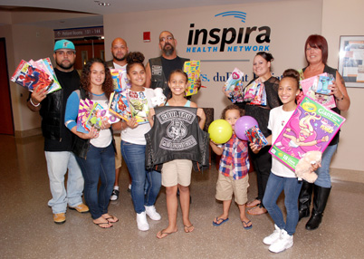 Members of Soul Tru stand with young patients at Inspira Medical Center Vineland.