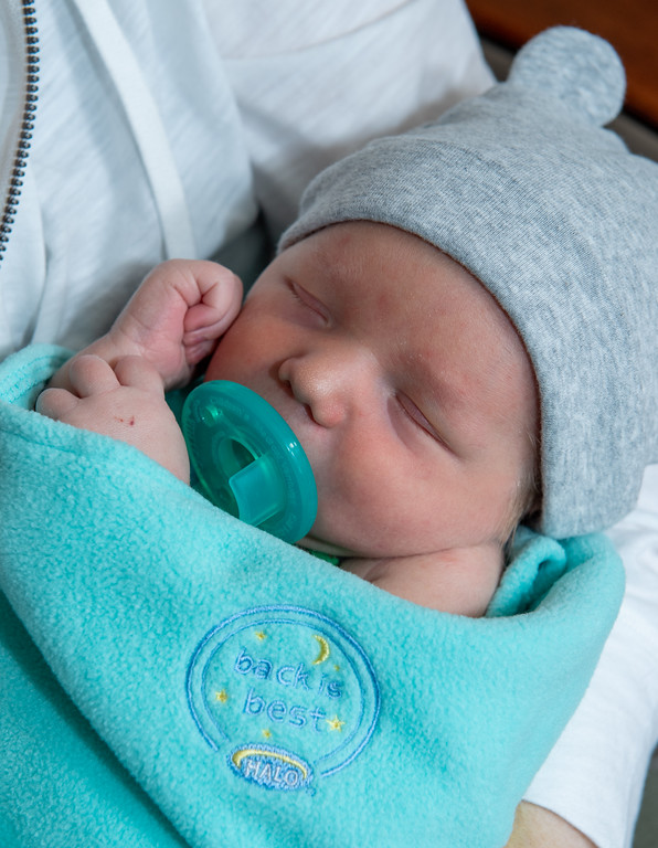 Close shot of a baby in a blue blanket wearing a hat with bear ears