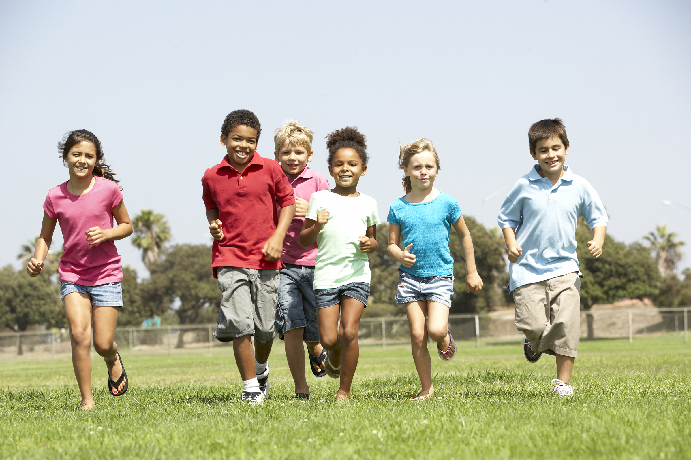A group of children running in a field
