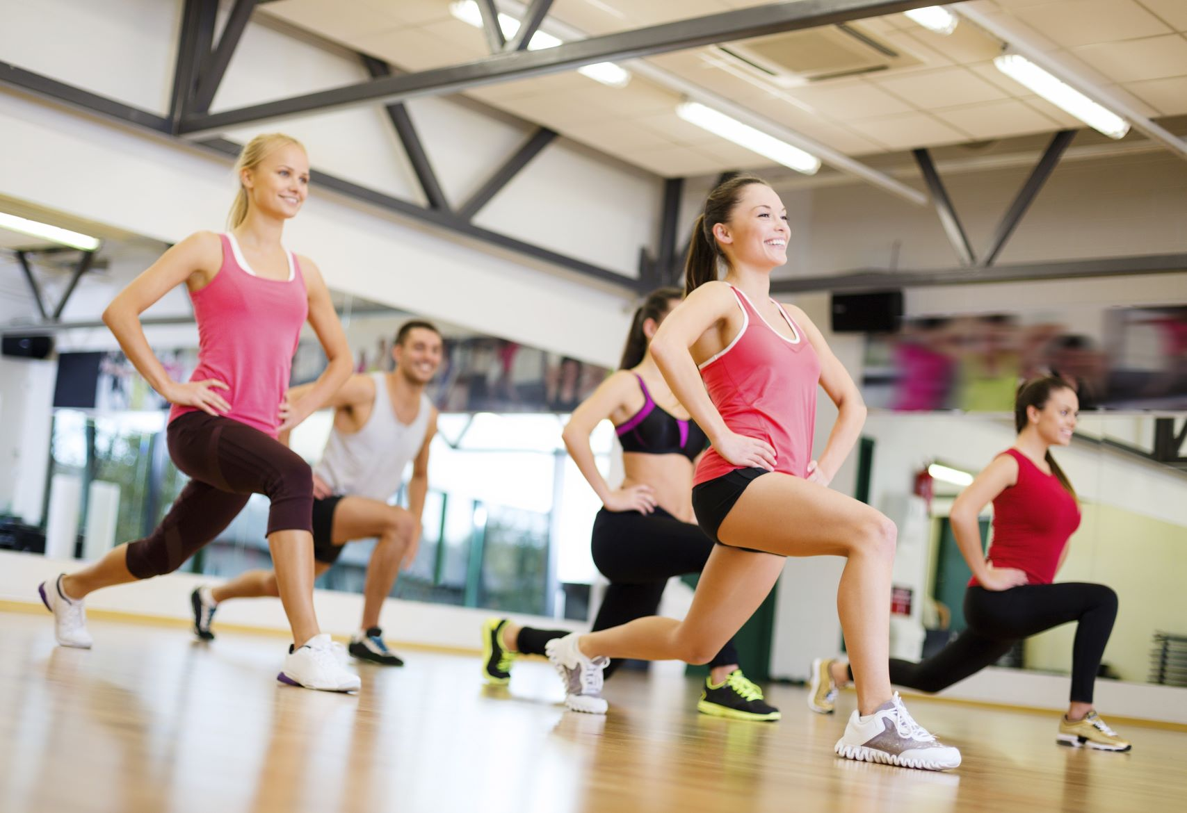 group of women in a gym class lunging