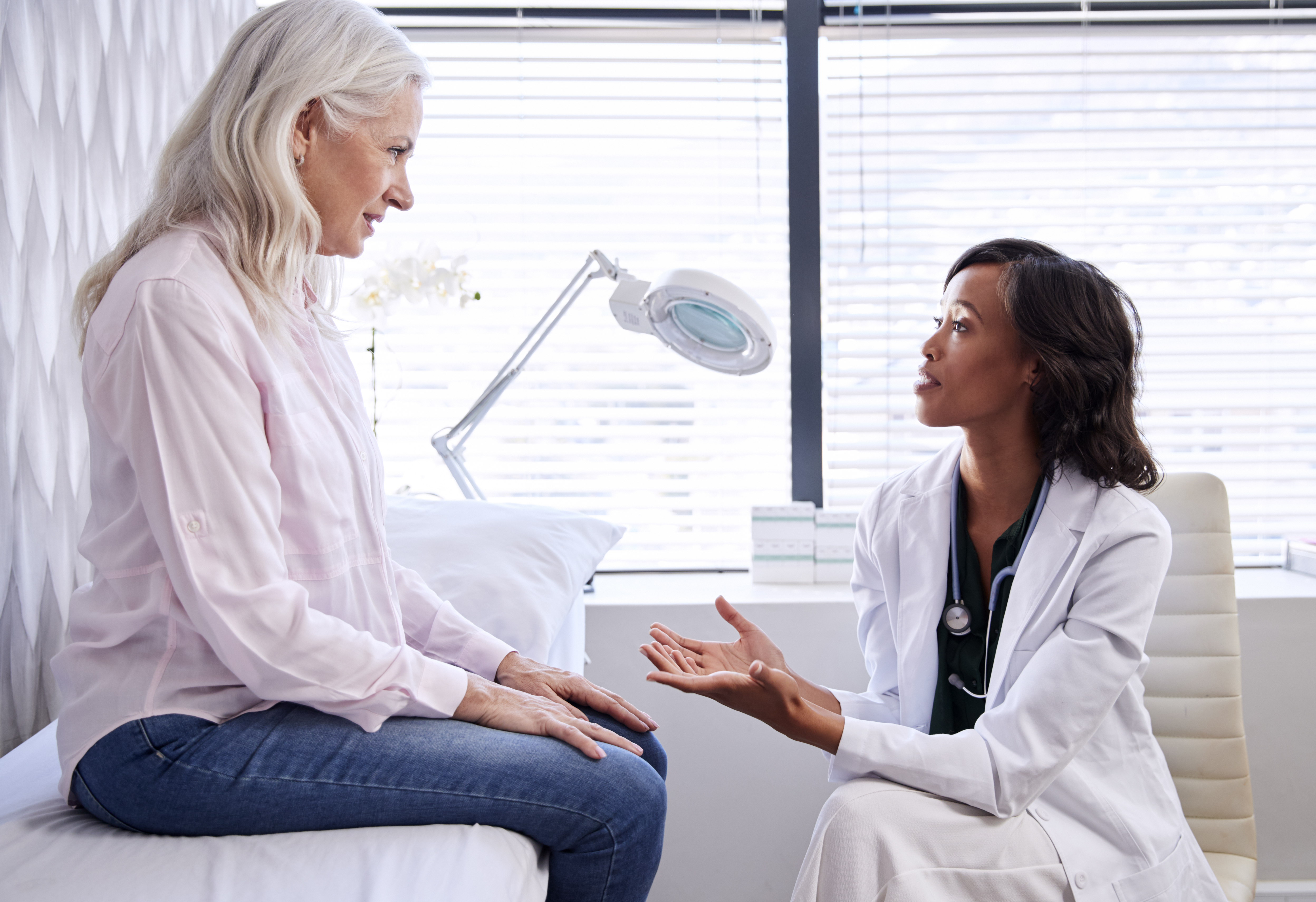 An older woman on a patient table talking with a doctor