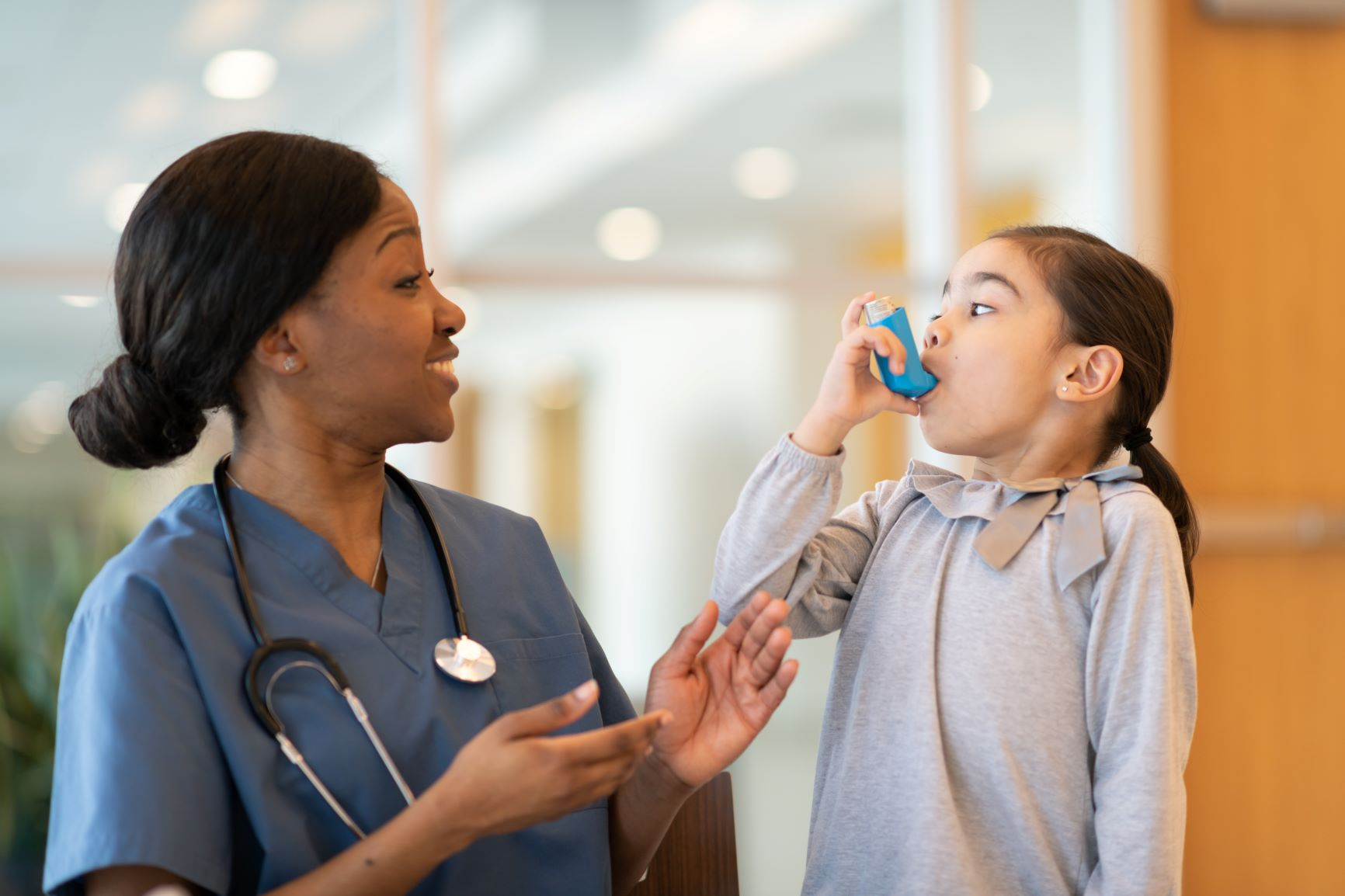 Smiling nurse cheering on little girl using an inhaler