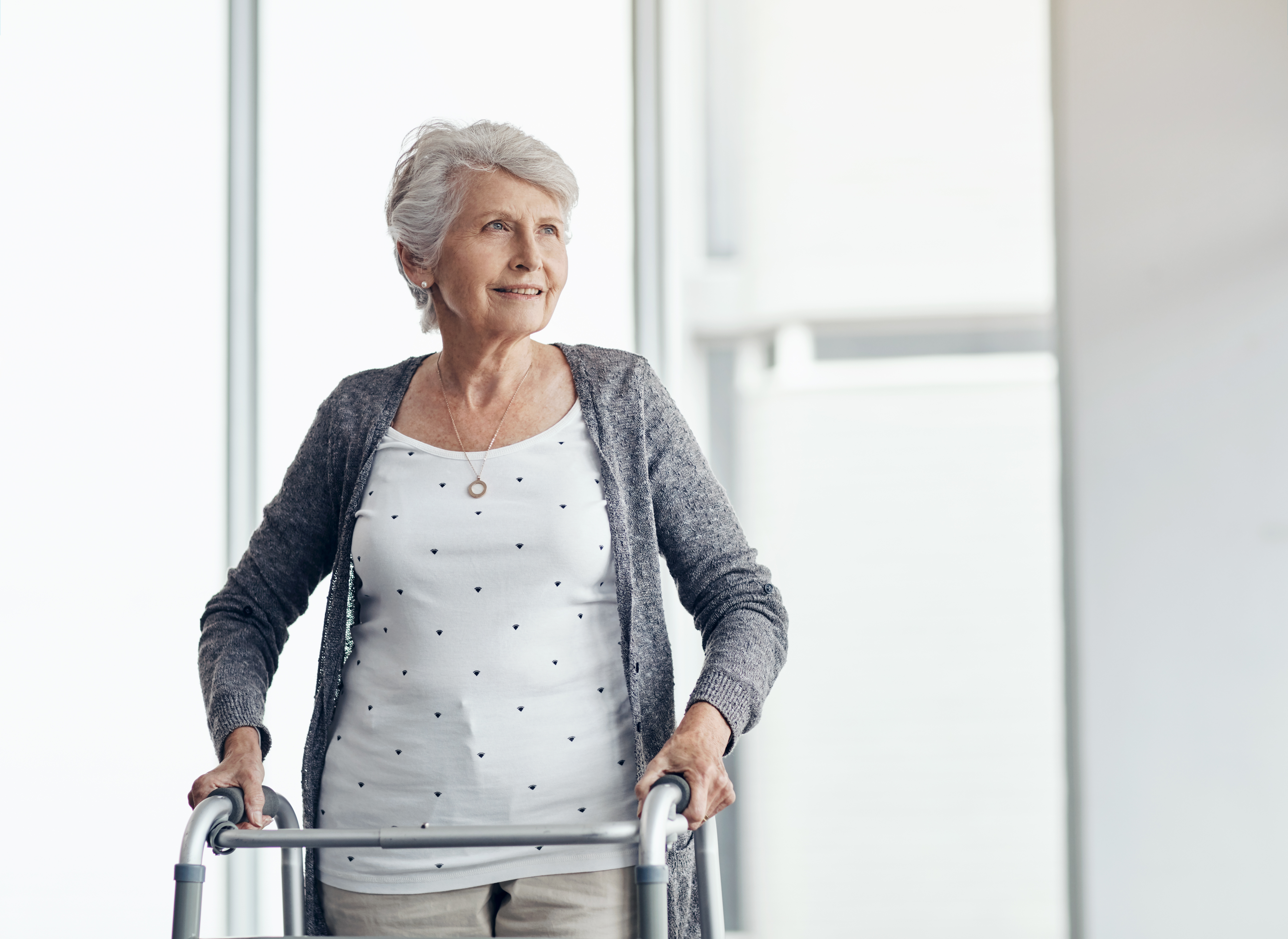 An older woman standing with a walker