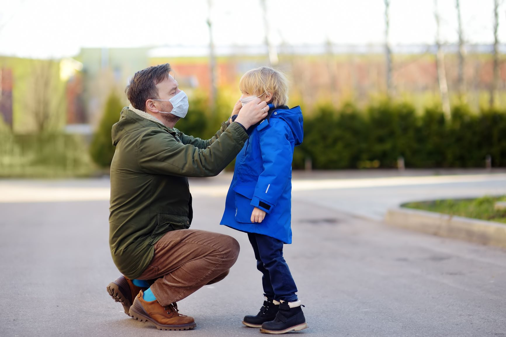 man wearing a jacket and a medical mask adjusting his son's medical mask outside