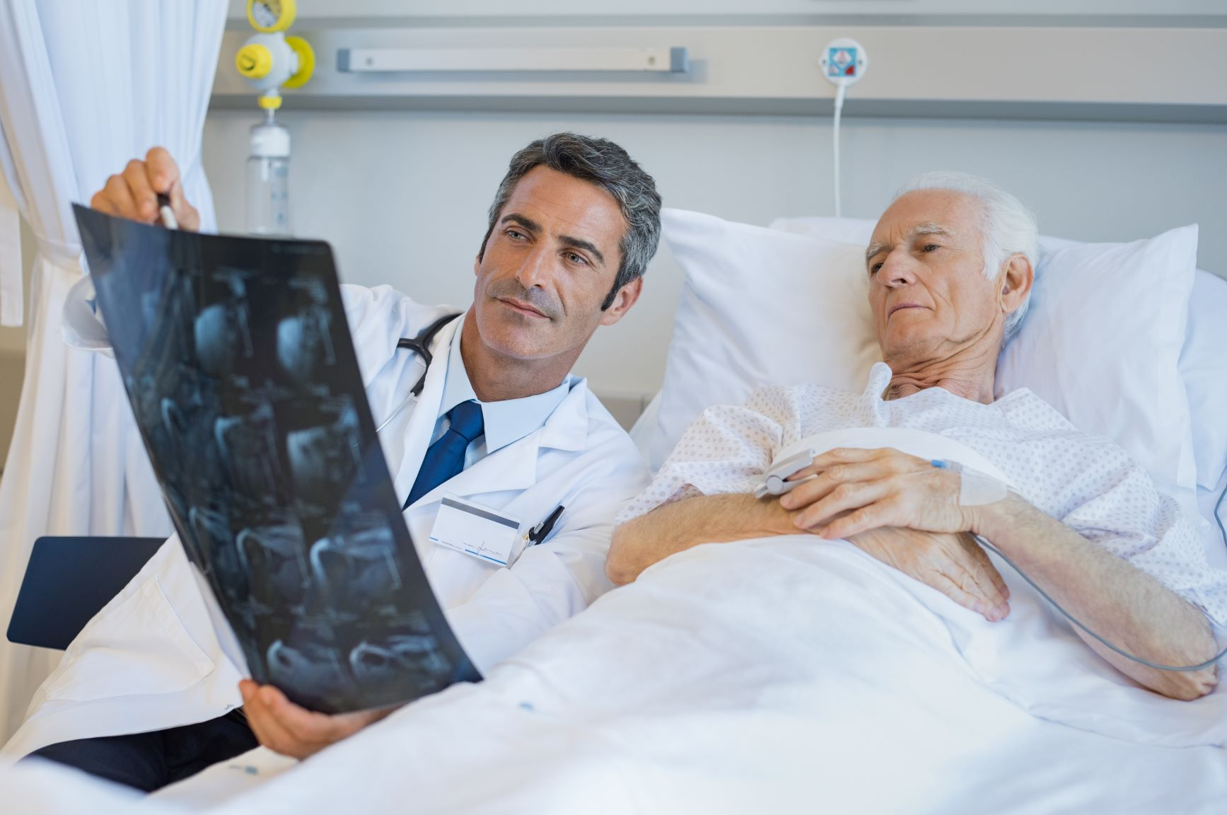 Male physician reviewing x-rays with an older male patient in a hospital bed