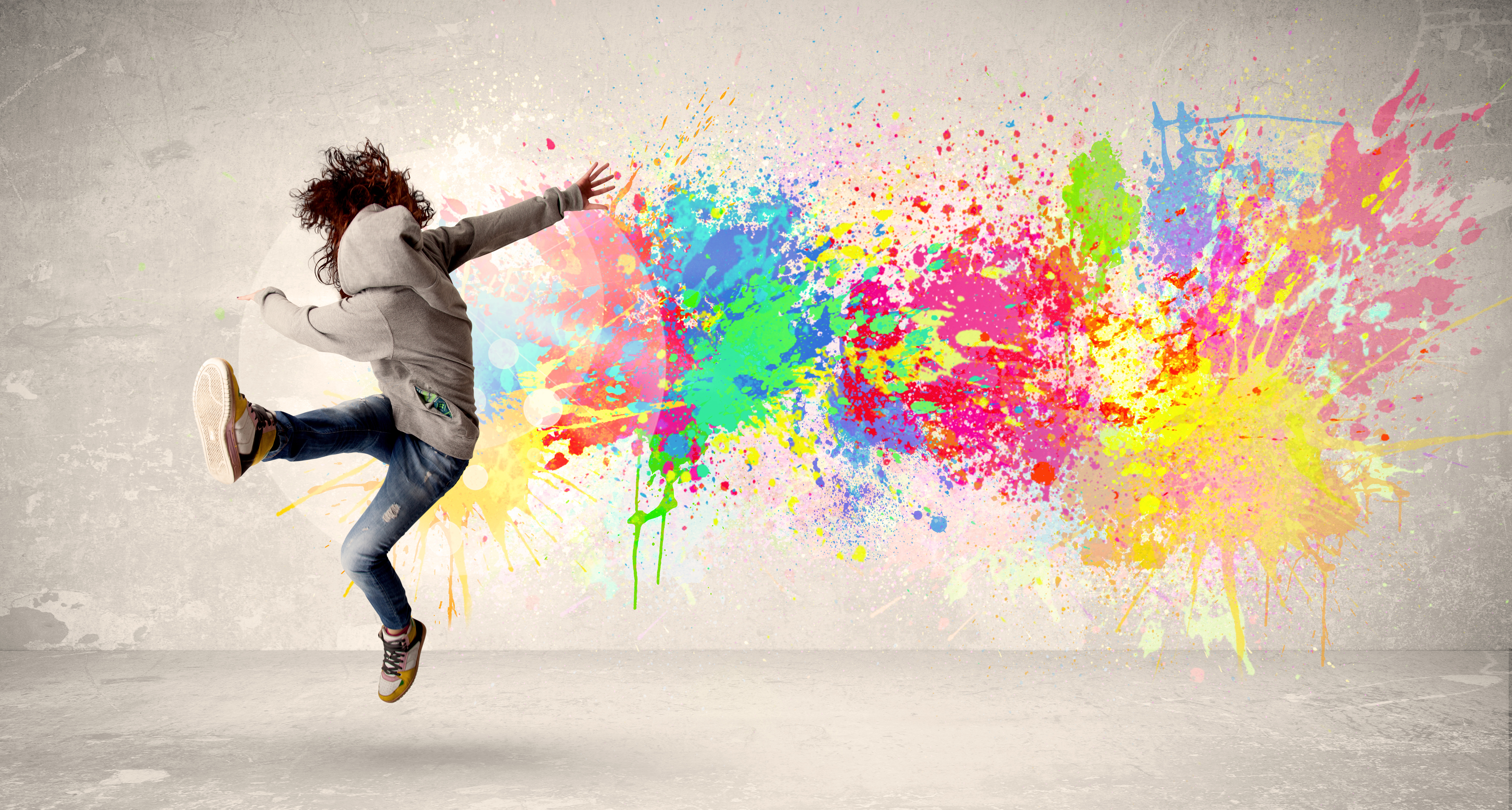 A person kicking one foot in the air with a colorful paint splatter on the wall behind them