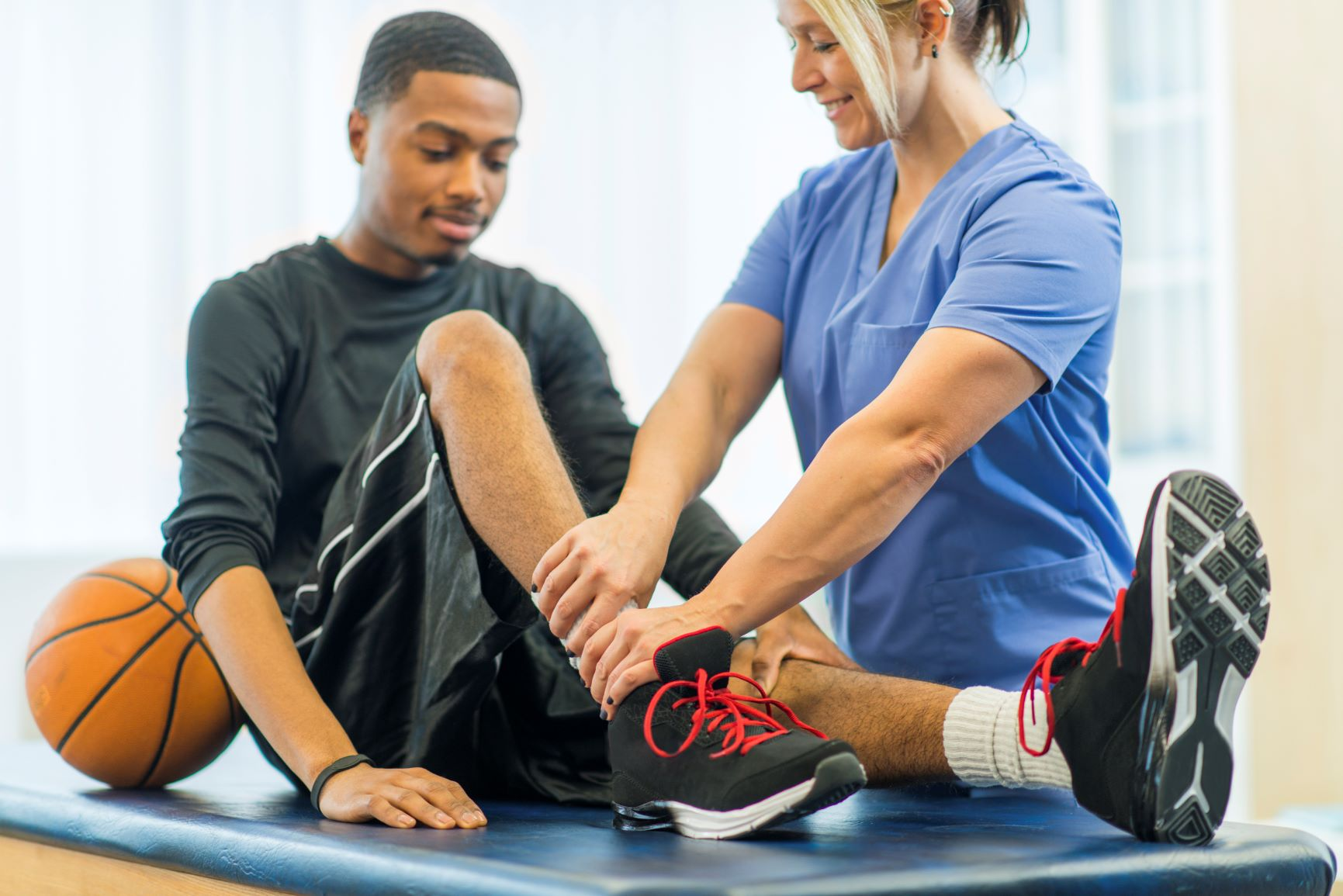 physician and male basketball player examining ankle