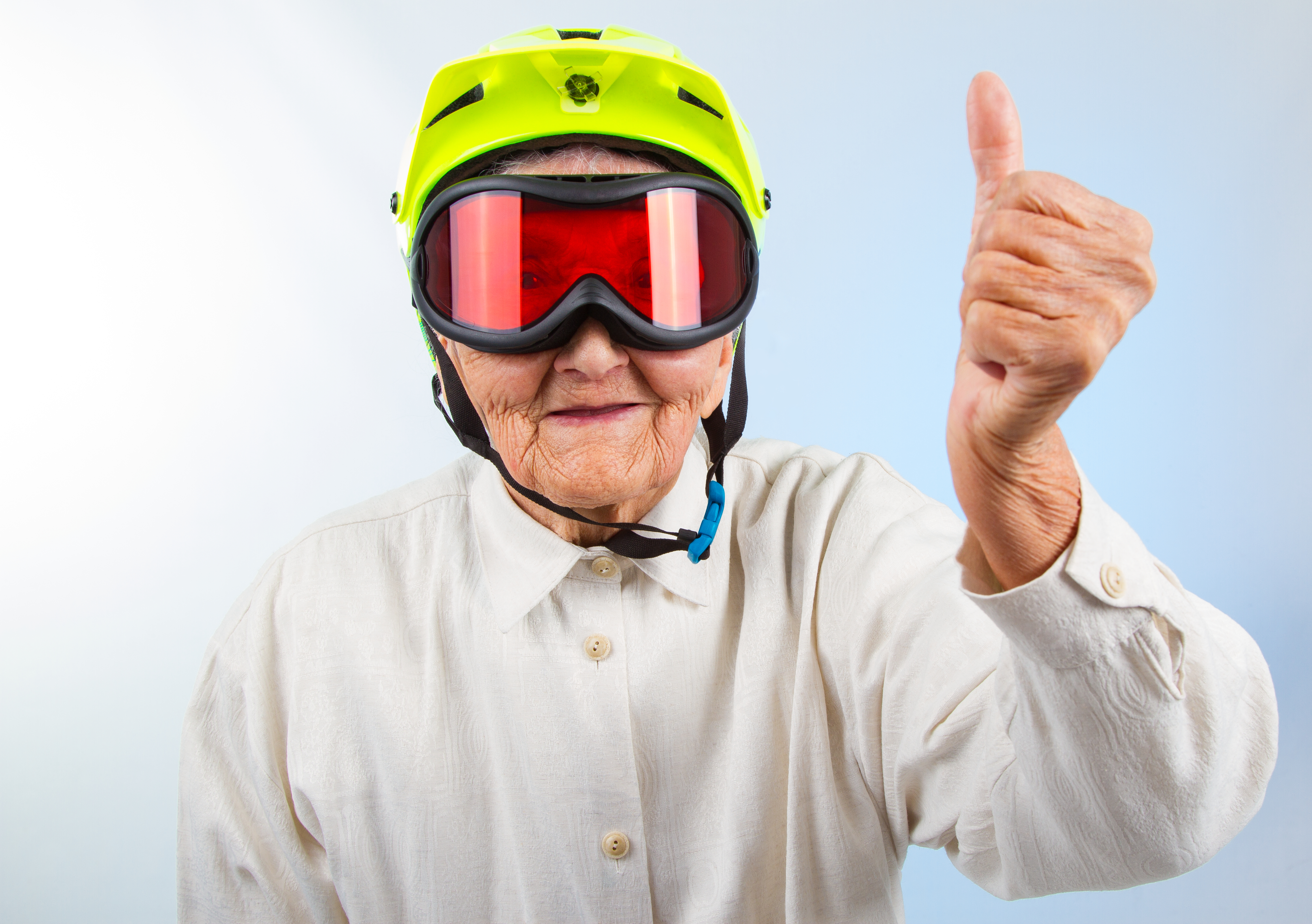 older man wearing a helmet and googles with a thumbs up