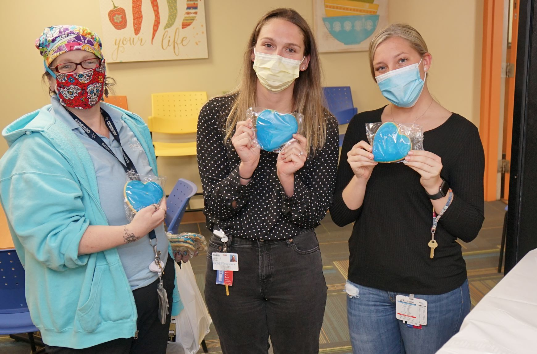 Bridgeton employees holding heart cookies and wearing masks