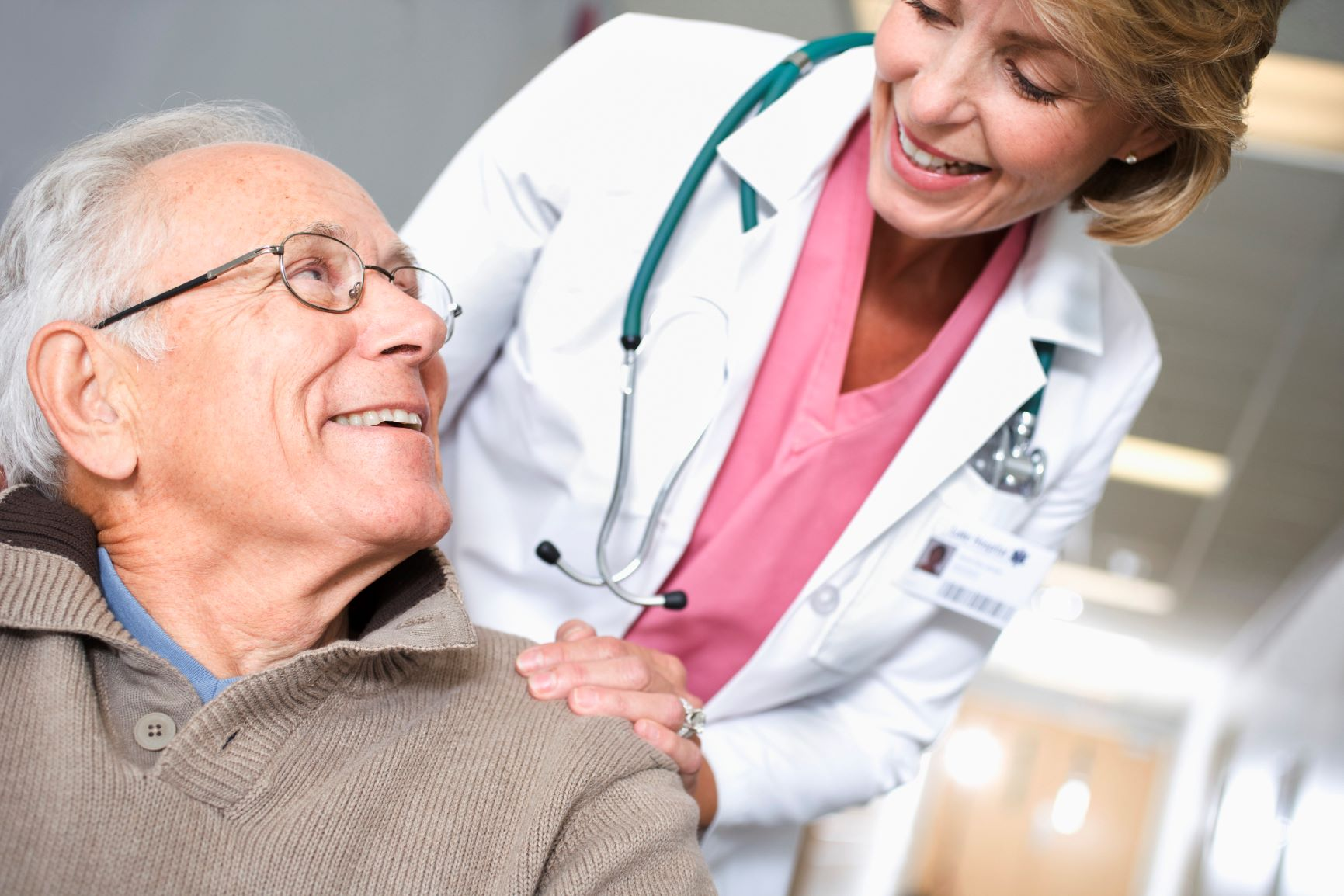 older man smiling up at a female physician