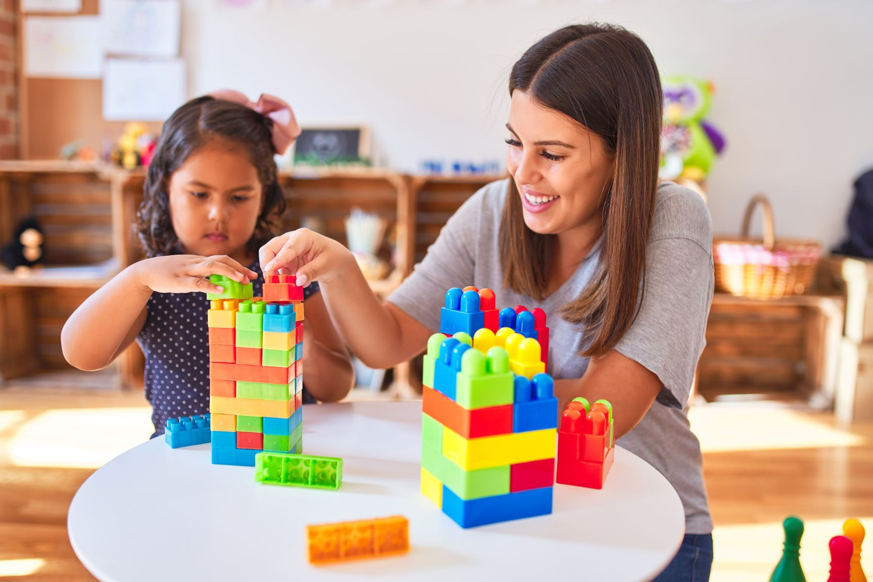 Beautiful teacher and toddler girl playing with construction blocks bulding tower at kindergarten
