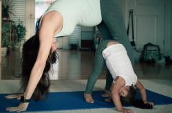 Pregnant woman doing yoga with a young child