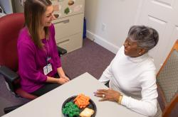 nutrition counselor sitting at a table with an older female patient with a plate of healthy food