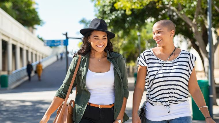 two women walking down a boardwalk smiling