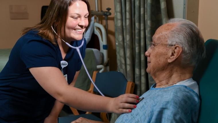 Smiling nurse using a stethoscope to listen to a senior man's chest