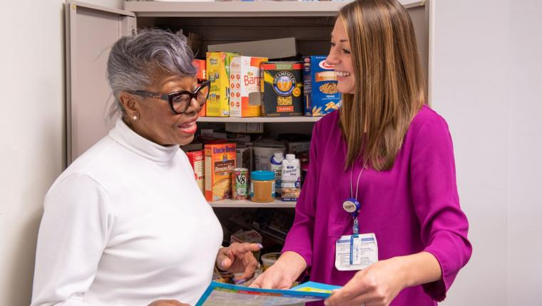 Nutrition counselor reviewing paper with patient in front of open pantry with healthy foods