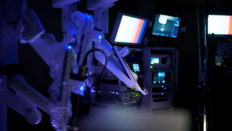 Robotic surgery equipment lit up in a dark room