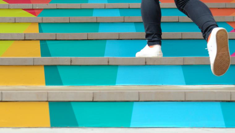 Someone wearing white sneakers walking up a colorful staircase