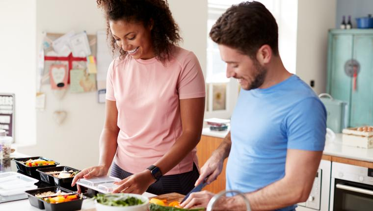 smiling man and woman doing meal prep