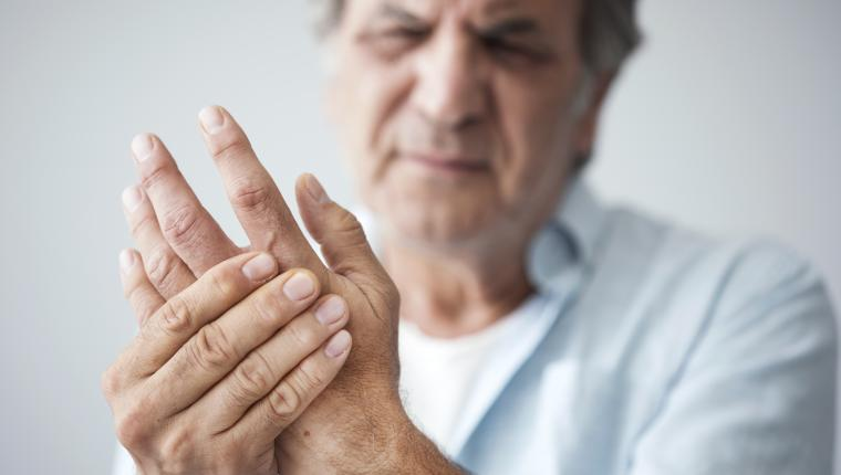 An older man cringing and holding his hand in pain
