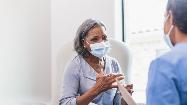 woman wearing a medical mask talk to a physicians in a medical office