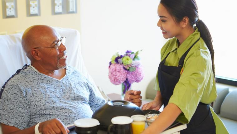 Senior Male Patient Being Served Meal On Tray In Hospital Bed