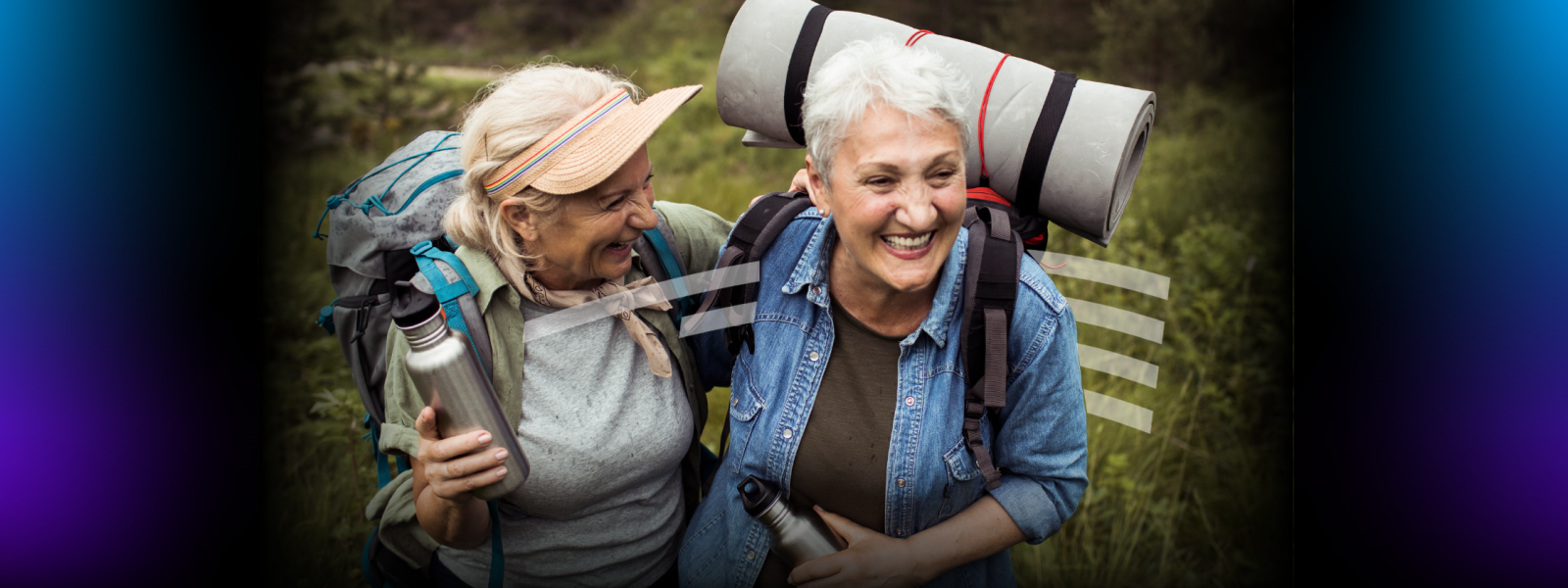 two older women laughing and hugging while hiking and carrying reusable water bottles and backpacks