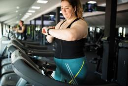 Woman on a treadmill checking her watch