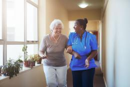Senior woman who is very happy being helped down a sunny hallway with a smiling nurse