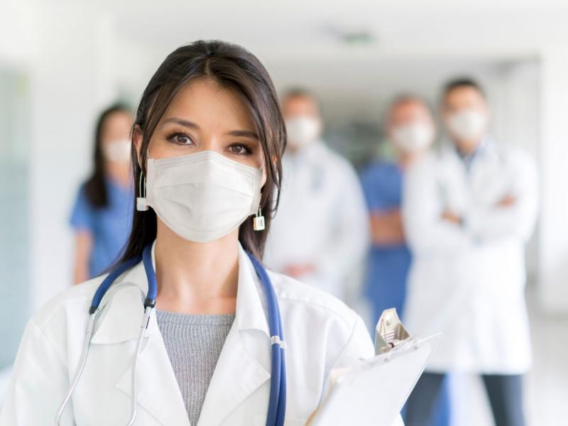 Portrait of a female doctor working at the hospital wearing a facemask to avoid COVID-19 with staff at the background