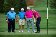 amy mansue putting on the green with a group of men behind her