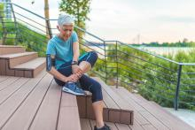 older woman in exercise clothes rubbing her ankle on steps outside