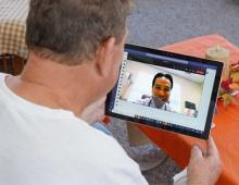 man viewing an ipad during a telehealth appointment with a physician