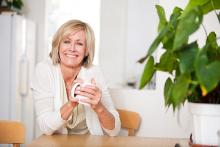 cheerful middle aged woman sitting at a table drinking from a mug