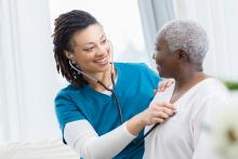 Cheerful mid adult home healthcare nurse checks a senior female patient's lungs. She is using a stethoscope.