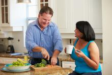 Overweight Couple On Diet Preparing Vegetables In Kitchen Whilst Talking To Each Other