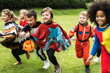 children in halloween costumes running outside