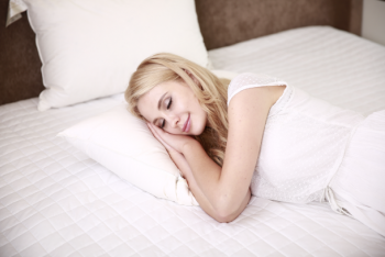 Female sleeping on a white bed