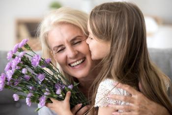 olderwoman being given flowers and a kiss on the cheek by young girl