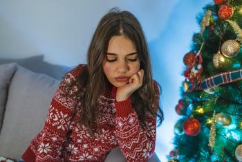 sad woman in sweater next to a christmas tree