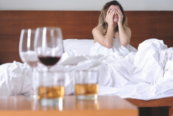 Exhausted woman in bed with wine and tumblers on a nearby table