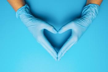Gloved hands on a blue background forming a heart