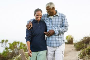 Senior african american couple casually dressed waling together on a boardwalk outdoors near the beach.