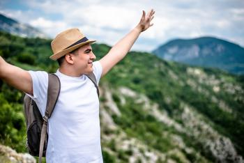 Man wearing a backpack and a heat with his arms raised outside